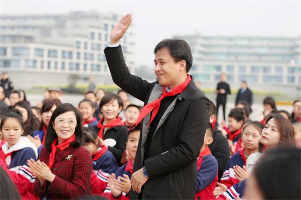 图为:网龙首席执行官熊立博士戴上红领巾共同参与节目录制