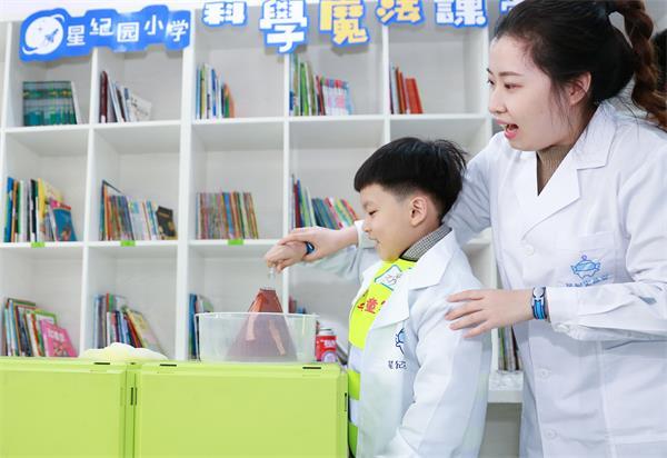 图为:网龙星纪园学校的老师带领孩子们体验科学魔法课