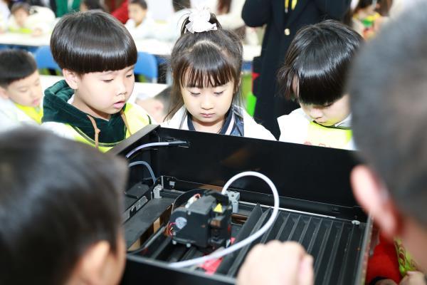 图为:孩子们观察3D打印机的工作原理