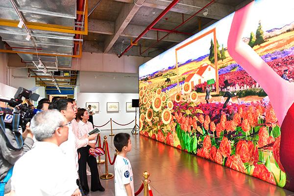 眾多參觀者在藝數花海互動大屏前駐足體驗
